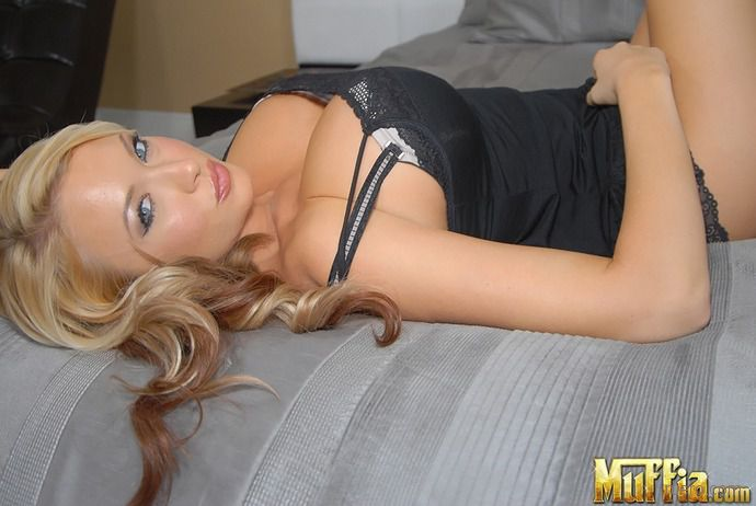 Hot blonde with big boobs posing on bed.
